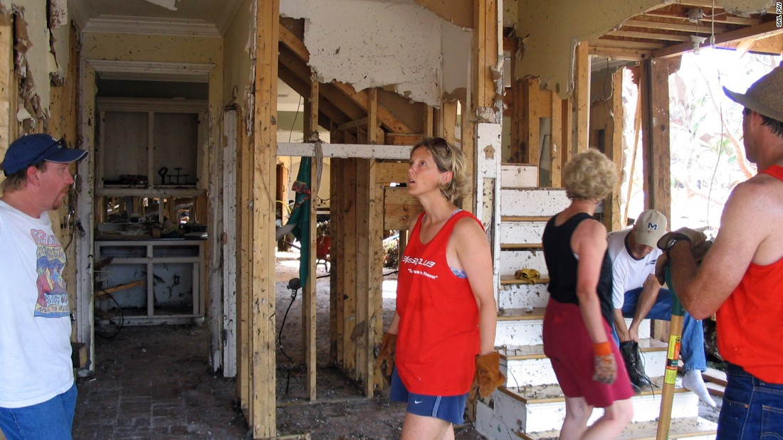 A group of neighbors surveys the damage in one home.