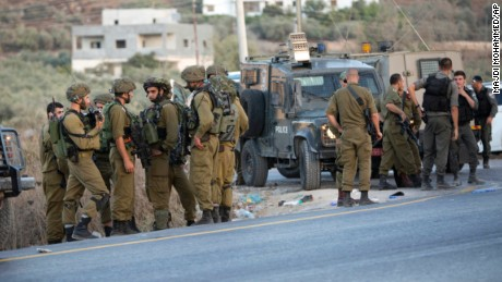 Israeli soldiers gather after a Palestinian was shot and killed by an Israeli policeman after he stabbed a policeman, in the village of Beita south of the West Bank city of Nablus.