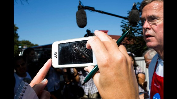 "A reporter uses a cracked smart phone to record Bush. The Republican presidential candidate has become widely known for his weight loss on the ""Paleo"" diet."