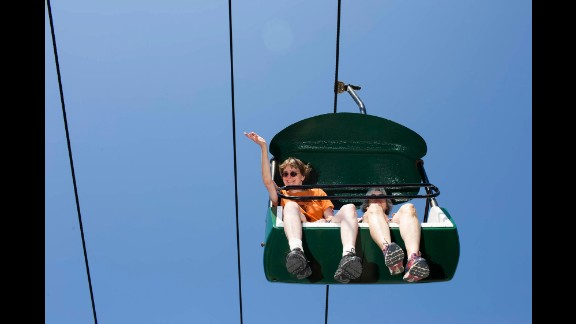 A woman riding a chairlift waves at Bush.