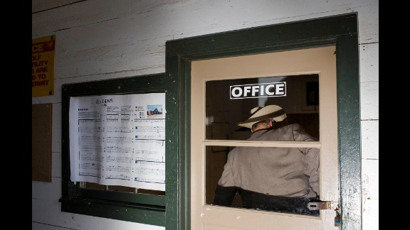 A man in a cowboy hat stands inside the office of the Horse Barn.