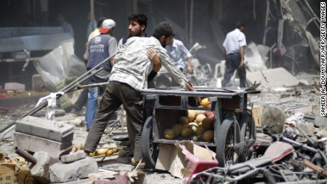 Syrian men react as they stand amid the rubble following air strikes by Syrian government forces on a marketplace in the rebel-held area of Douma, east of the capital Damascus, on August 16, 2015. At least 82 people were killed and 250 people were injured, with the death toll -most of them civilians- likely to rise as many of the wounded were in serious condition, the Syrian Observatory for Human Rights said. AFP PHOTO / SAMEER AL-DOUMY        (Photo credit should read SAMEER AL-DOUMY/AFP/Getty Images)