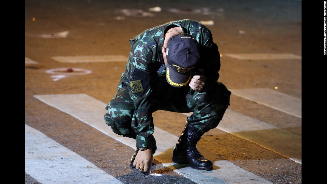 A Thai Army officer collects evidence in the street.