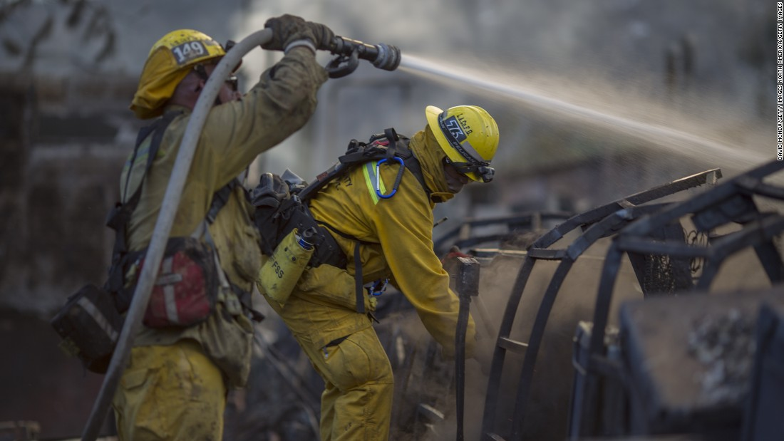 Firefighters hose down the smoldering ruins of a building that was burned by the Warm Fire north of Castaic, California, on Sunday, August 16.