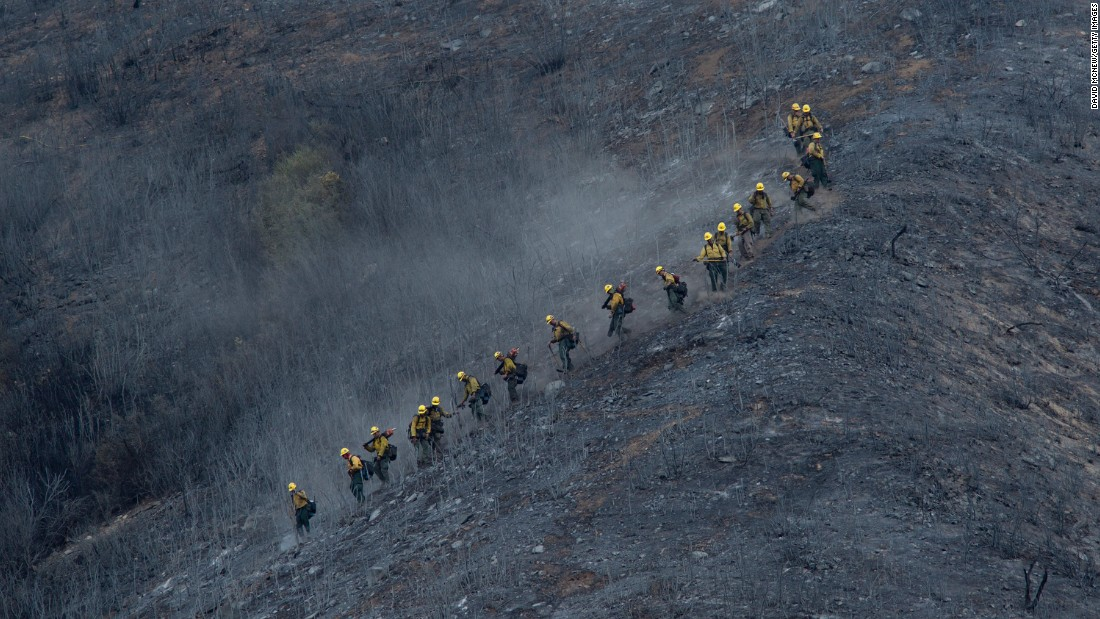 A crew descends a scorched mountainside in the Angeles National Forest on August 15.