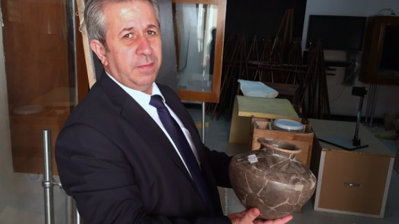 Maamoun Abdulkarim, Syria's Director-General of Antiquities and Museums, holds an ancient vase retrieved from the northeast city of Deir Ezzor.