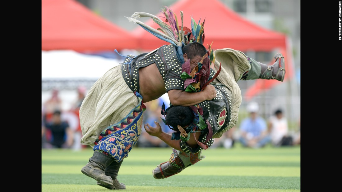 Two men compete in Mongolian wrestling Sunday, August 16, during the National Traditional Games of Ethnic Minorities of China.