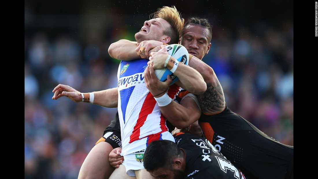 Nathan Ross of the Newcastle Knights is tackled by several of the Wests Tigers during a National Rugby League match in Sydney on Saturday, August 15.