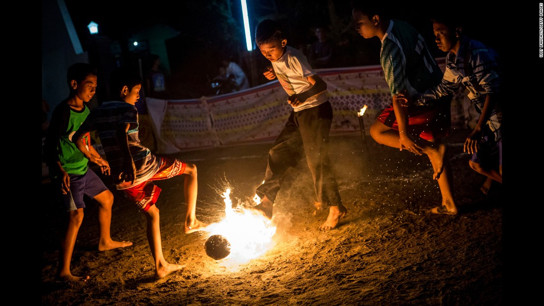 "Children in Yogyakarta, Indonesia, play a game of fire soccer known as ""bola api"" on Saturday, August 15. The game is played with a coconut that is soaked in kerosene and set on fire."