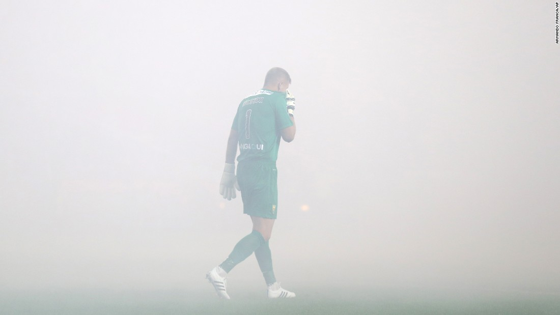 Estoril goalkeeper Pawel Kieszek is engulfed in smoke during a league match in Lisbon, Portugal, on Sunday, August 16. The smoke came from fireworks lit by supporters of the Lisbon club Benfica.