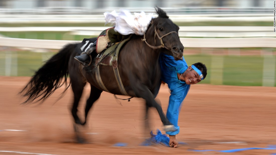 "A Mongolian rider picks up ""hadas,"" or scarves, while riding a horse Sunday, August 16, at the National Traditional Games of Ethnic Minorities of China."