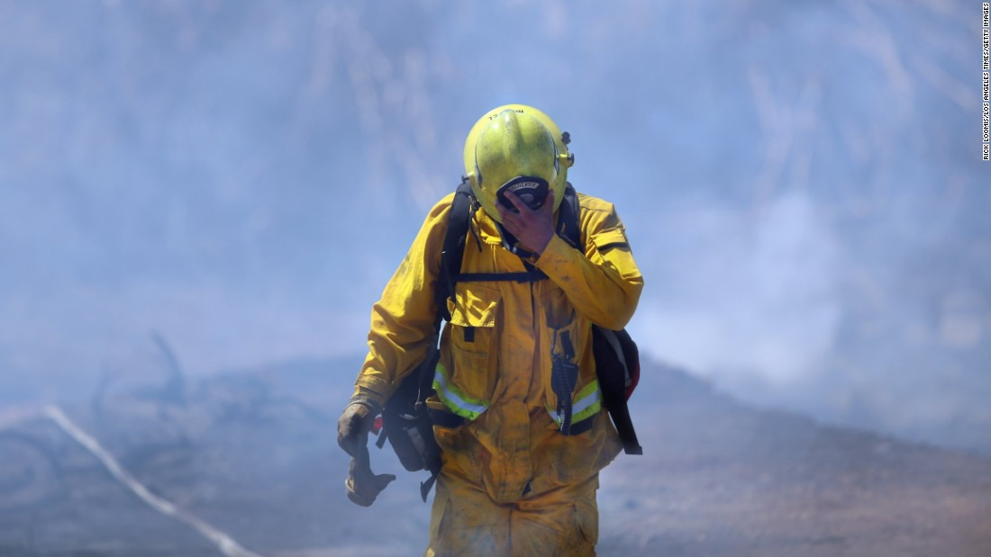 Firefighter Mike Martel walks through smoke while working to clean up after a weekend fire that ravaged the Montebello Hills area near Los Angeles on Monday, August 17.