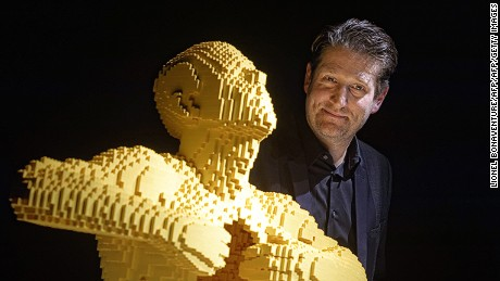 "US artist Nathan Sawaya poses next to his artwork at the exhibition ""The Art of the brick"" in Paris on May 12, 2015. Nathan Sawaya replicates iconic classical artworks with millions of LEGO building blocks.  AFP PHOTO / LIONEL BONAVENTURE RESTRICTED TO EDITORIAL USE, MANDATORY MENTION OF THE ARTIST UPON PUBLICATION, TO ILLUSTRATE THE EVENT AS SPECIFIED IN THE CAPTION"