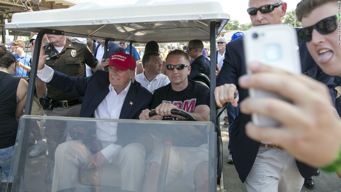 "A man tries to take a selfie as Republican presidential candidate Donald Trump, red hat, rides past him in a golf cart at the Iowa State Fair on Saturday, August 15. <a href=""http://www.cnn.com/2015/08/15/politics/gallery/iowa-state-fair-postcards/"" target=""_blank"">See more photos of presidential candidates at the Iowa State Fair </a>"