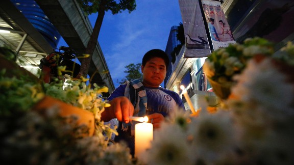 A Thai lights a candle near the Erawan Shrine  the day after the explosion in Bangkok.