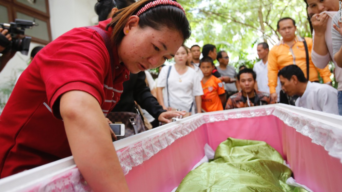 Family members gather around the coffin of a bombing victim on Tuesday, August 18. The death toll from the bomb blast in the Thai capital stood at 20 with more than 120 wounded, police said.
