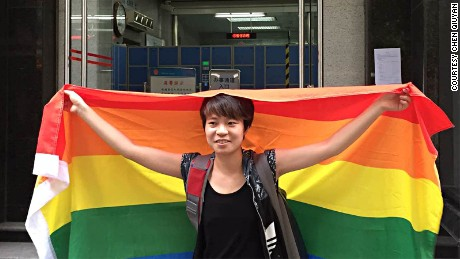 Chinese student Chen Qiuyan holds a rainbow flag, protesting in front of an intermediate court in southern China city Guangzhou on July 29, 2015.