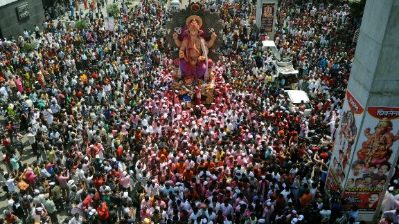 Indian Hindu devotees gather around a huge idol of the elephant-headed Hindu god Lord Ganesha during the procession for immersion into the Arabian Sea, on the streets of Mumbai on September 29, 2012.