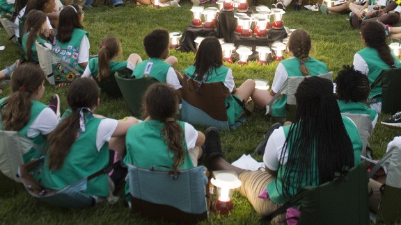 """US President Barack Obama and First Lady Michelle Obama talk with Girl Scouts that are camping overnight on the South Lawn of the White House in Washington, DC, June 30, 2015. Fifty Girl Scouts will spend the night on the White House lawn in camping tents as part of the """"Let's Move"""" campaign to fight childhood obesity and increase nutrition awareness. AFP PHOTO / SAUL LOEB        (Photo credit should read SAUL LOEB/AFP/Getty Images)"""