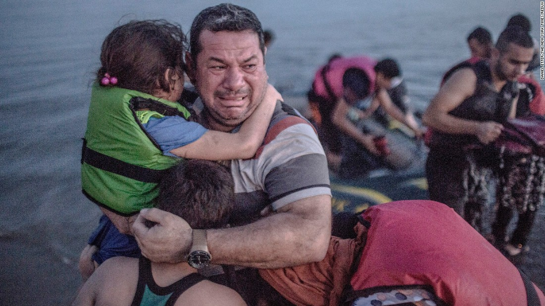 A refugee, holding his son and daughter, cries tears of joy after their boat arrived on the Greek island of Kos on Saturday, August 15. The island in the Aegean Sea has been overwhelmed by Syrian refugees.