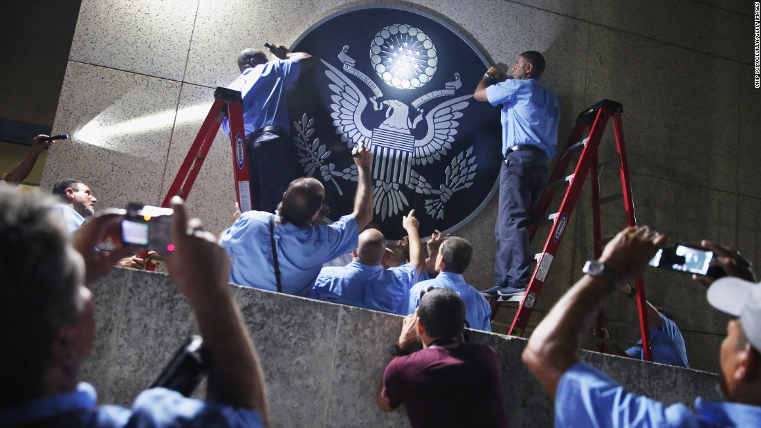 U.S. Embassy employees in Havana, Cuba, hang the seal of the United States on the outside of the building a few hours before its ceremonial flag-raising on Friday, August 14. Cuba and the United States re-established diplomatic relations in July.