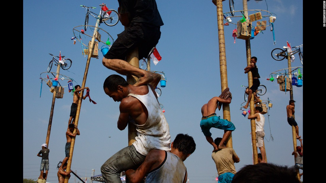 Men in Jakarta, Indonesia, climb greased poles for prizes during Independence Day celebrations on Monday, August 17.