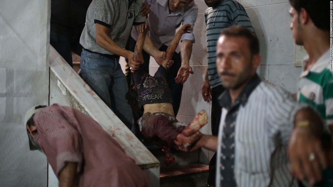 A child is carried away for medical care after being wounded in a bomb strike in Damascus, Syria, on Sunday, August 16.