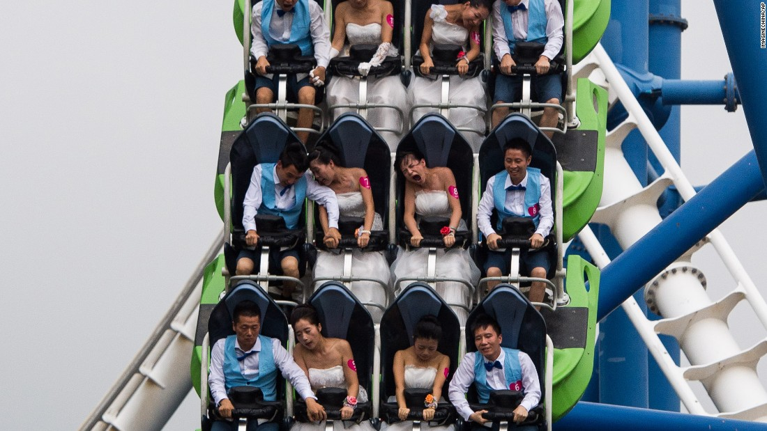 Couples ride a roller coaster during a group wedding ceremony at a Shenzhen, China, amusement park on Thursday, August 20.