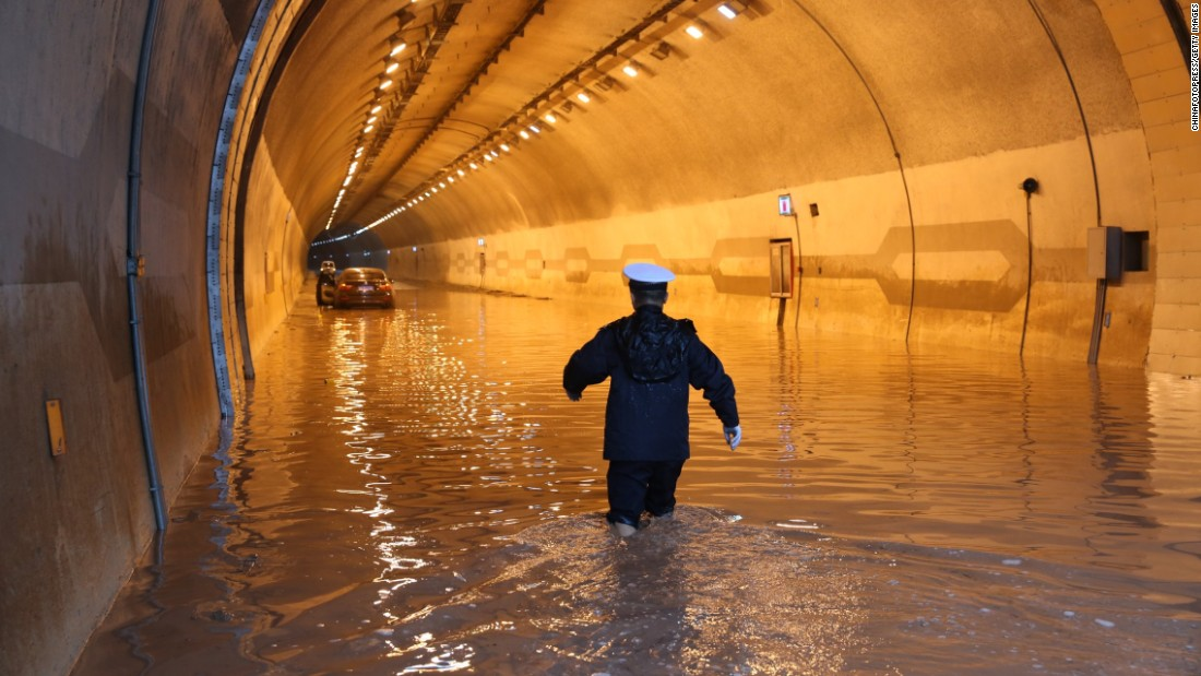 A police officer in Chonqing, China, moves toward a trapped car in a flooded tunnel on Monday, August 17.