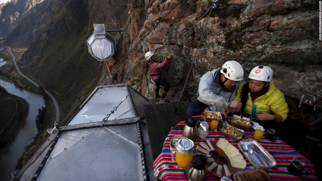Climbers have breakfast on the steep face of a cliff in Peru's Sacred Valley on Friday, August 14.