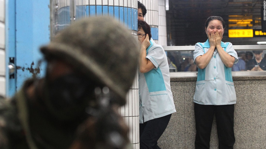 Subway station workers watch a soldier aim his weapon during an anti-terror drill in Seoul, South Korea, on Wednesday, August 19.