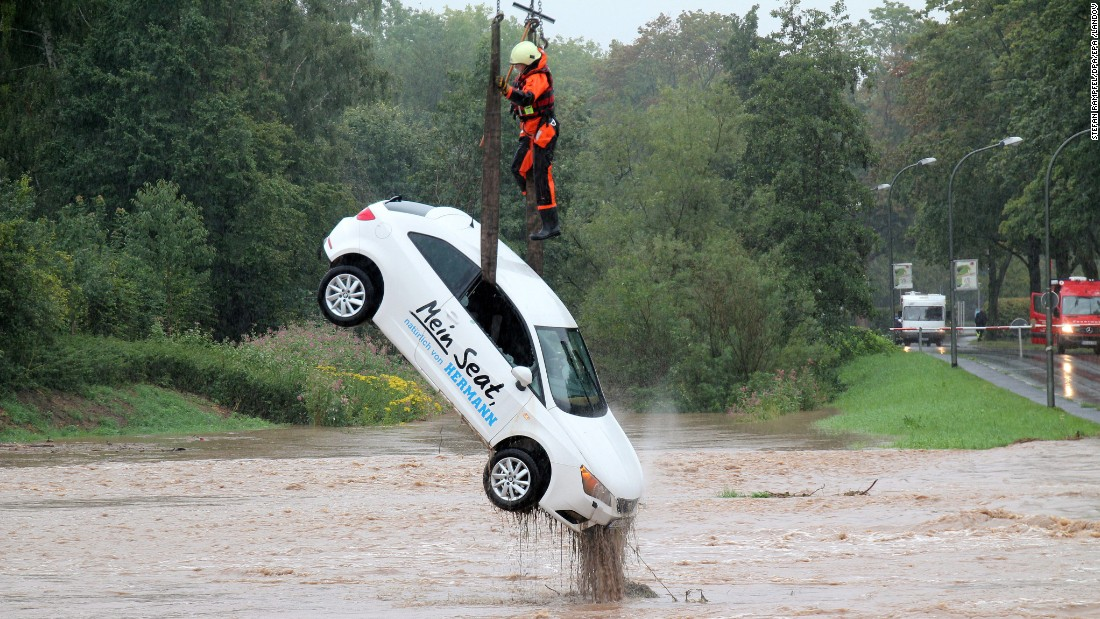 A firefighter stands on a car attached to a crane as it is recovered from a flooded area in Gottingen, Germany, on Monday, August 17.