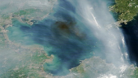 A dark plume of smoke drifts over the Bohai Sea off the east coast of China. The source of the smoke appears to be industrial fires caused by explosions at a port in Tianjin, China. The streams of light gray smoke in the image likely were caused by wildfires in eastern China. NASA