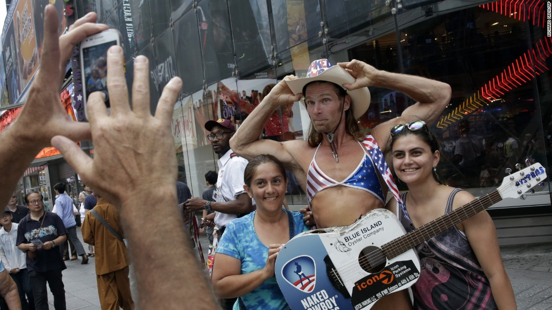 Robert Burck, who performs as the Naked Cowboy, poses for photos in New York's Times Square on Wednesday, August 19.