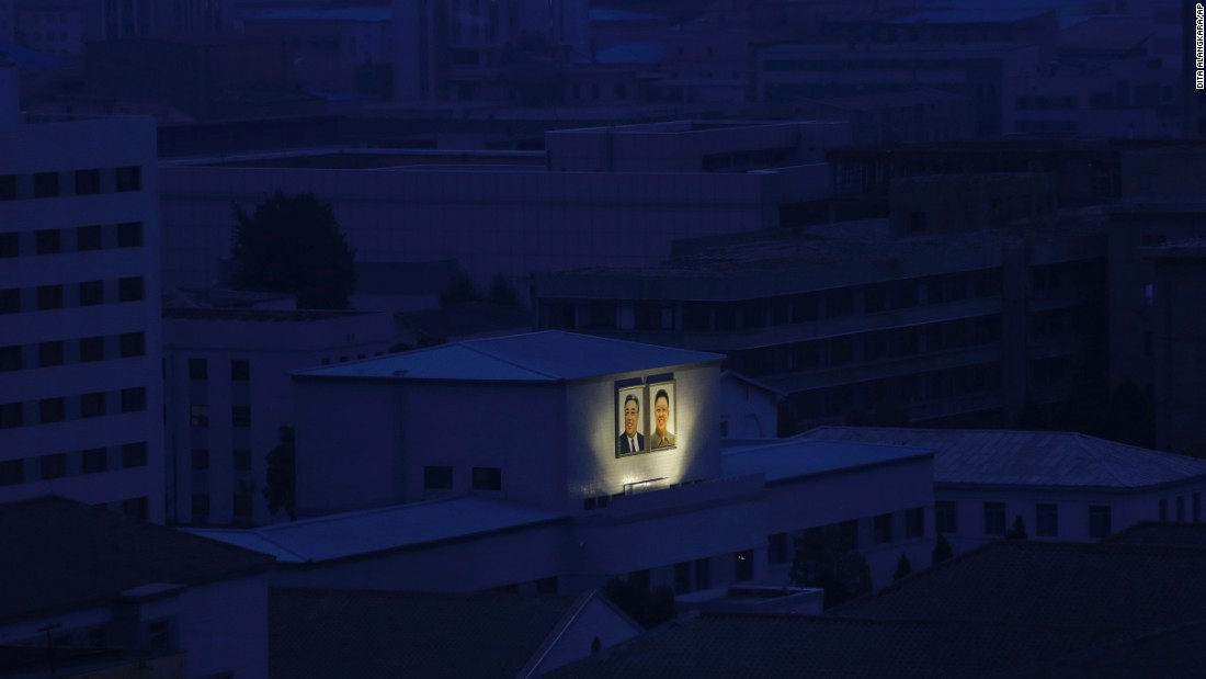 Portraits of the late North Korean leaders Kim Il Sung, left, and Kim Jong Il are illuminated at dawn in Pyongyang, North Korea, on Wednesday, August 19.