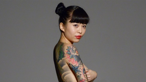 Wang Ke, a Chinese tattoo artist, shows her tattoos as she holds a placard saying,