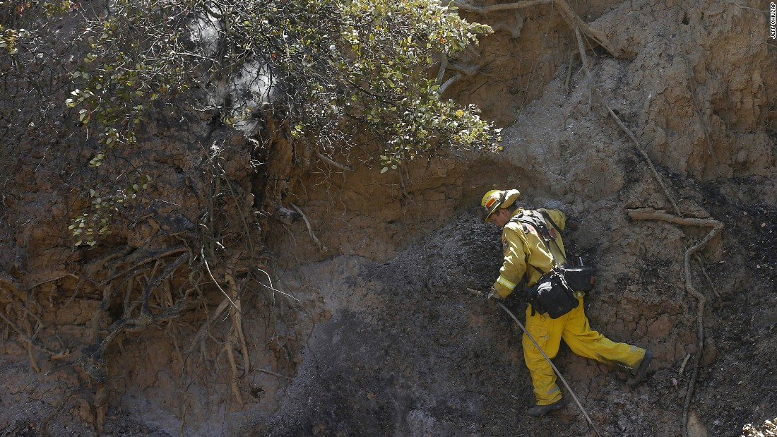 A firefighter climbs on the side of a hill while putting out hot spots in Livermore on August 20.