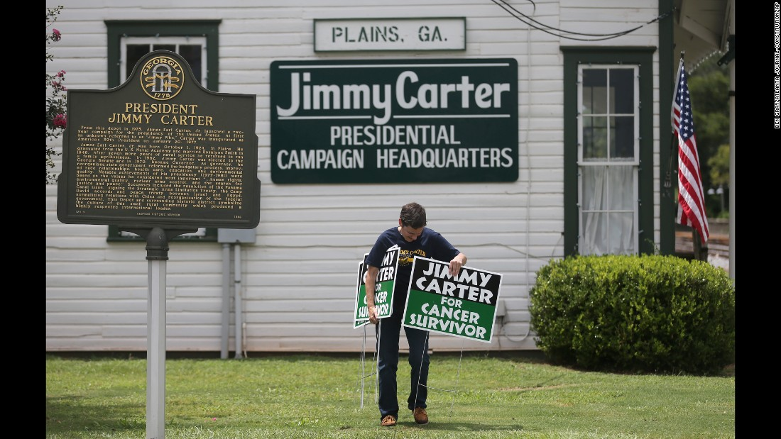 "Jill Stuckey places signs in front of Jimmy Carter's former campaign headquarters in Plains, Georgia, on Thursday, August 20. During a news conference in Atlanta that day, the former U.S. President <a href=""http://www.cnn.com/2015/08/20/politics/jimmy-carter-cancer-update/index.html"" target=""_blank"">announced that he has cancer spots on his brain</a> and will immediately begin a regimen of treatment."