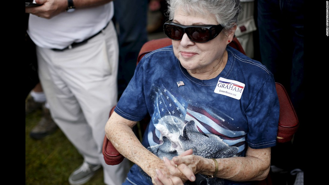 A woman at the Iowa State Fair listens to U.S. Sen. Lindsey Graham as the South Carolina Republican campaigns for President on Monday, August 17.