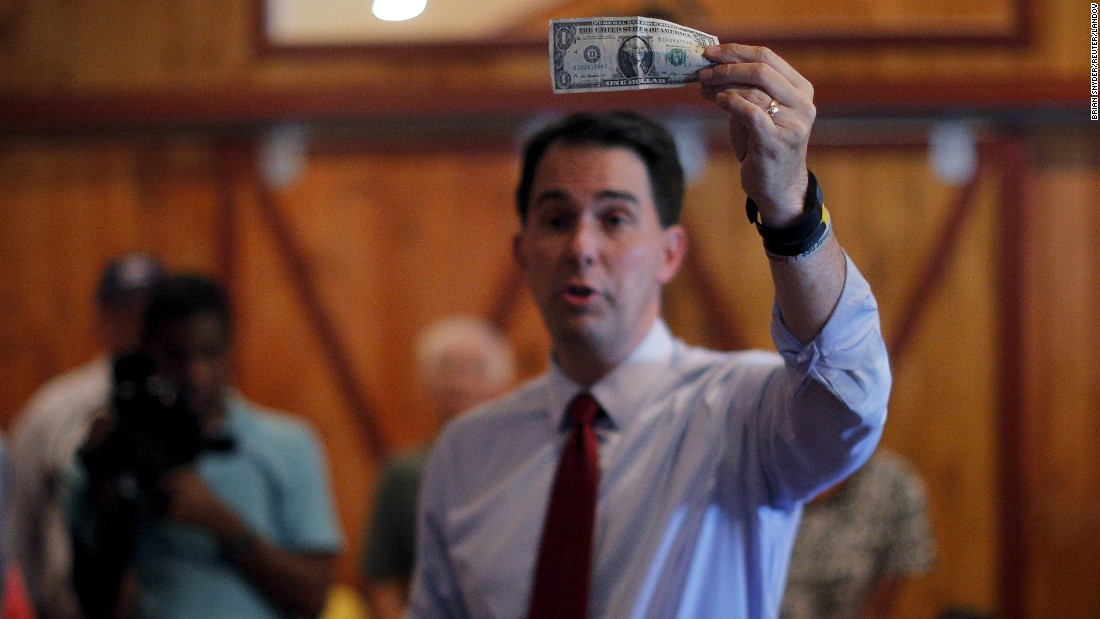Wisconsin Gov. Scott Walker, a Republican presidential candidate, holds up a $1 bill while talking to voters at a campaign stop in Sunapee, New Hampshire, on Thursday, August 20.