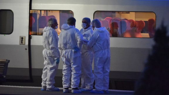 Police in protective suits stand on a platform next to the train.
