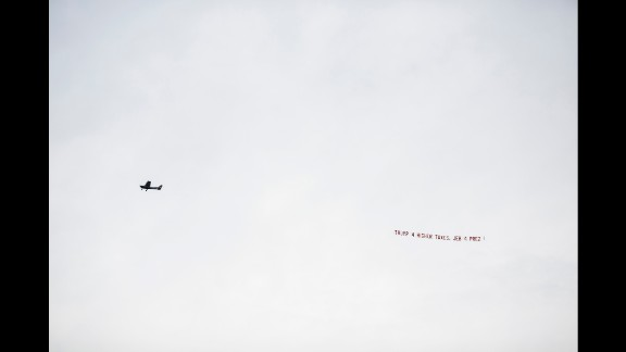 """A pro-Jeb Bush plane flies by the stadium with banner """"Trump 4 higher taxes. Jeb 4 Prez."""" Bush's official campaign said it emailed supporters in Alabama pointing out Trump's previous liberal positions on abortion, gun rights and tax issues."""