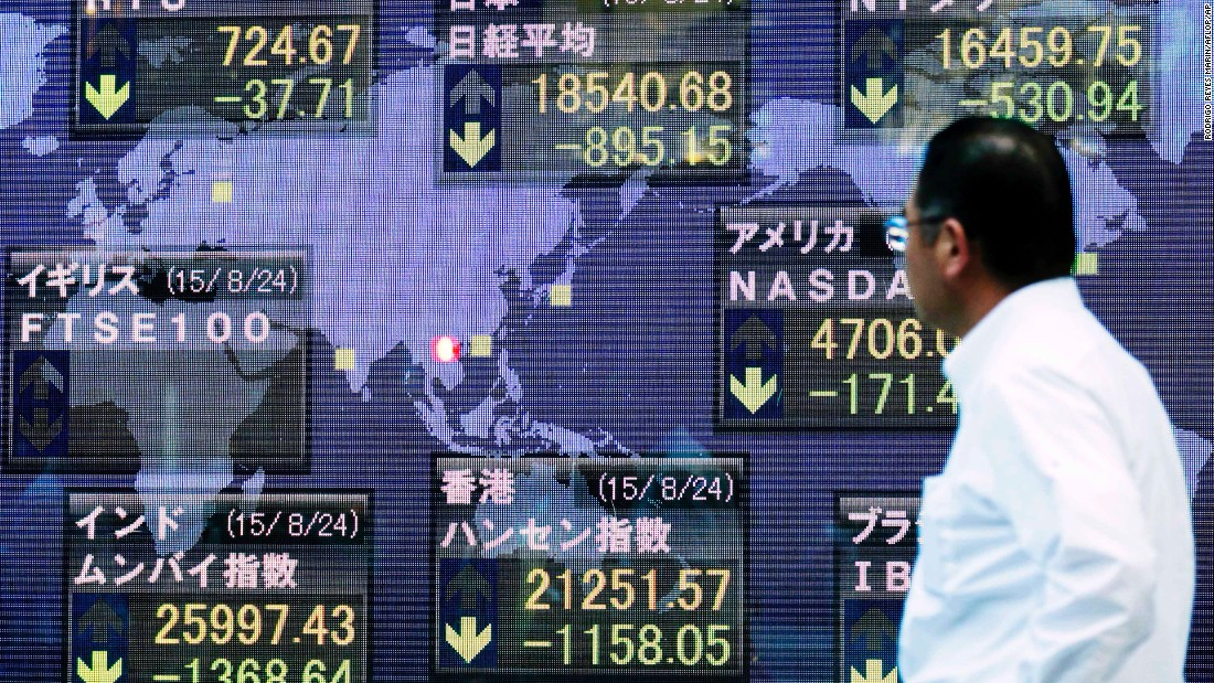 A man looks at the Nikkei Stock Average, which dropped 895.15 points, or 4.61%, at the end of trading on August 24 in Tokyo.