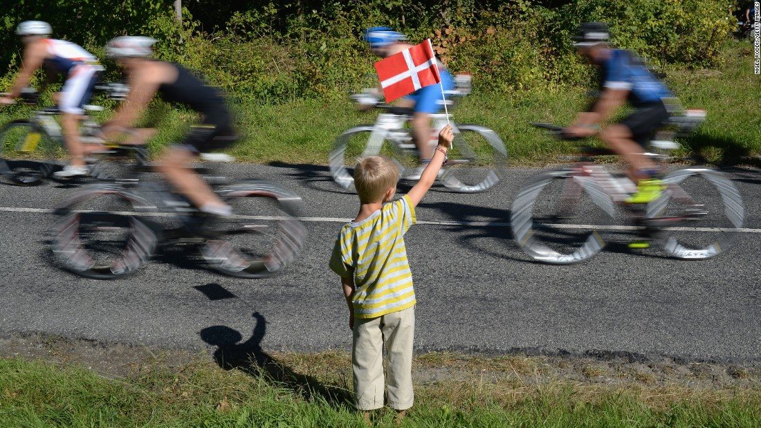 A boy waves the Danish flag as athletes compete in an Ironman race Sunday, August 23, in Copenhagen, Denmark.