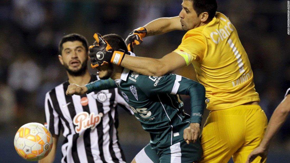 Libertad goalkeeper Rodrigo Munoz covers the face of Carlos Gonzalez, a forward for the Santiago Wanderers, as they vie for the ball during a Copa Sudamericana match Tuesday, August 18, in Asuncion, Paraguay. Libertad won the match 2-1 and advanced to the next stage of the tournament.