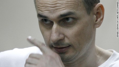 Ukrainian film director Oleg Sentsov looks out from a defendant's cage as he listens to the verdict.