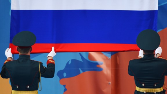 Russian guards unfold a Russian national flag during the podium ceremony of the Women's Solo Technical final during the synchronised swimming competition at the 2015 FINA World Championships in Kazan on July 25, 2015.  AFP PHOTO / CHRISTOPHE SIMON        (Photo credit should read CHRISTOPHE SIMON/AFP/Getty Images)