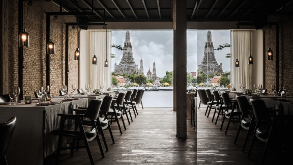 This Bangkok restaurant's design is from local practice Onion. Located on the banks of the Chao Phraya river, overlooking the legendary temple of the dawn (Wat Arun), modern interior design is folded into spiritual surroundings.   Design by Onion, Photo by Wison Tungthunya, W Workspace from Let's Go Out Again, Copyright Gestalten 2015