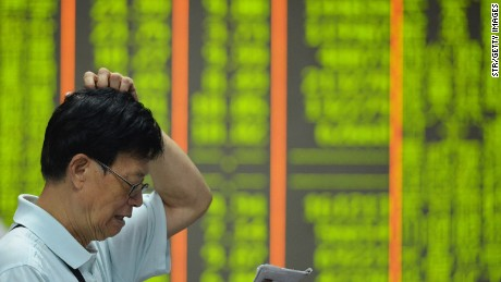 An investor reads a newspaper before a screen showing share prices at a securities firm in Hangzhou, in eastern China's Zhejiang province on August 24, 2015.  Shanghai shares nosedived 8.49 percent on August 24 as Beijing's latest market intervention failed to restore confidence, with concern mounting about the stalling economy.