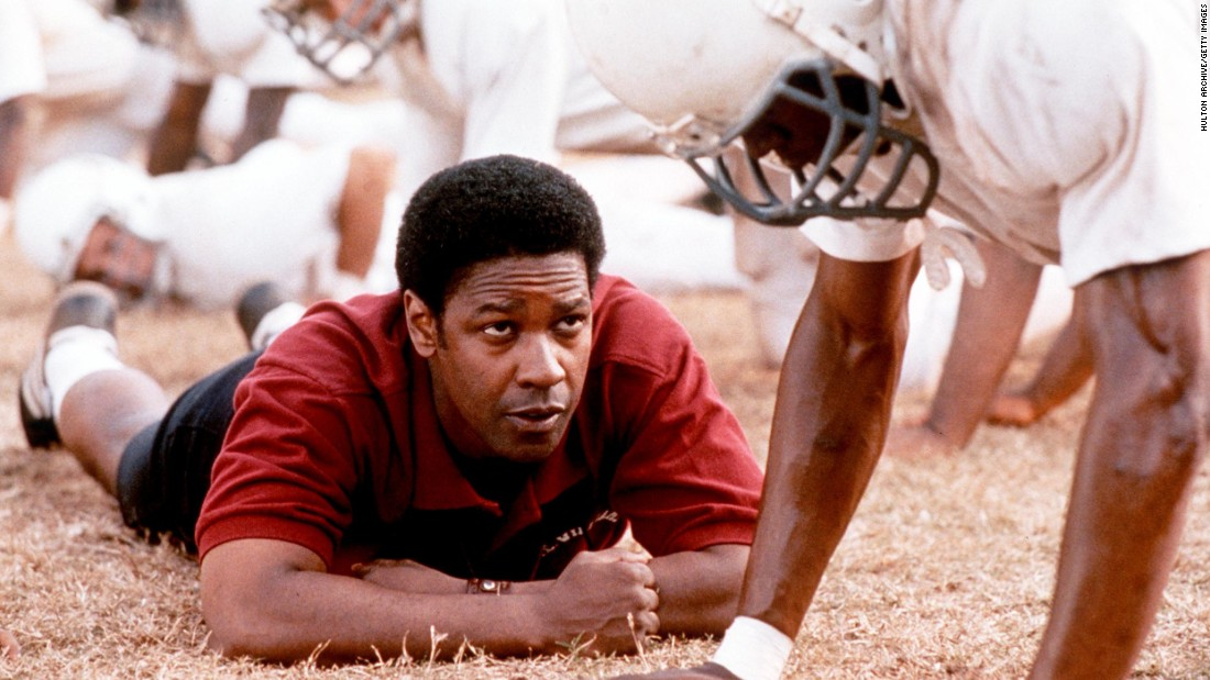 "Black and white high-schoolers play football together on the same team for the first time under the tutelage of a coach played by Denzel Washington in 2000's ""Remember the Titans."" The plot is based on a true story from the early 1970s."